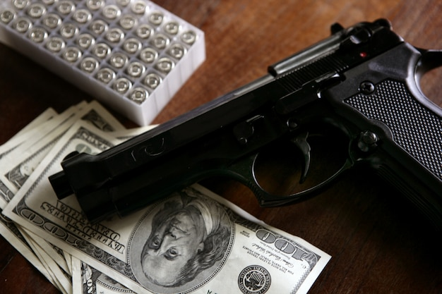 Долларовые банкноты и пистолет, черный пистолет