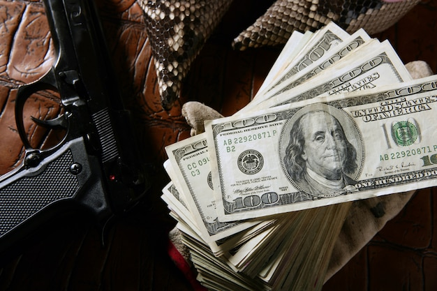 Долларовые банкноты и пистолет, черный пистолет, мафиозное вдохновение