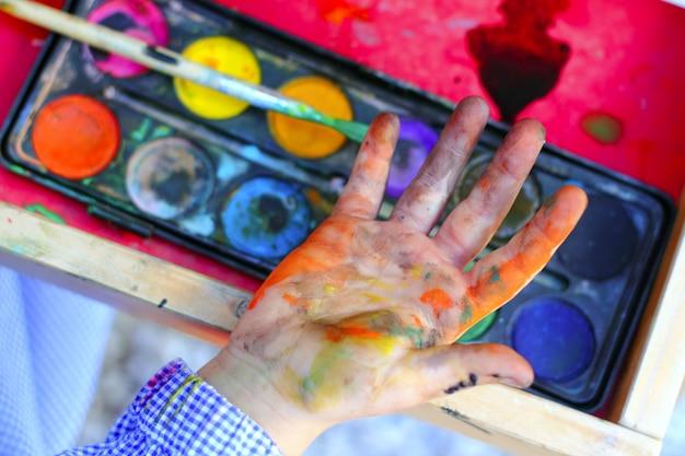 アーティストの子供たちが筆の手を塗る
