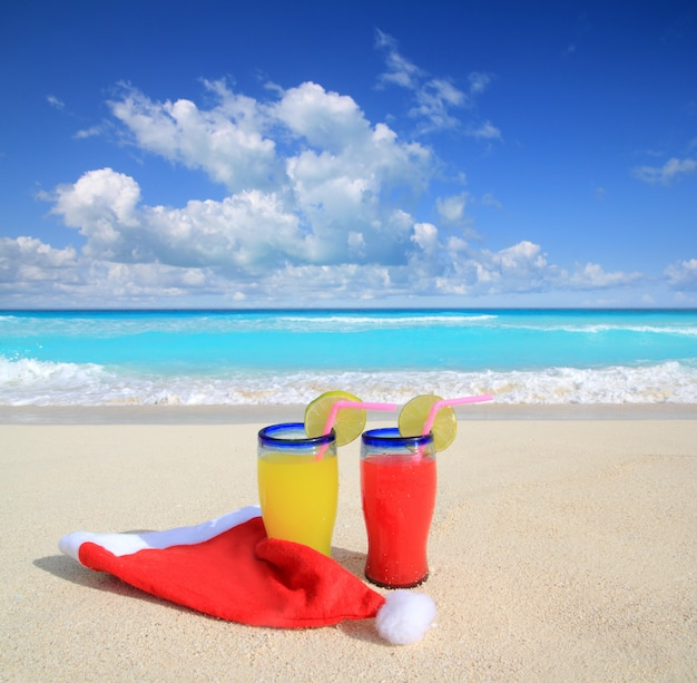 Пляжные коктейли с красной новогодней шапкой санта-клауса