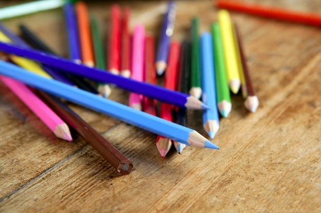 木製の机の上にカジュアルなカラフルな鉛筆の配置