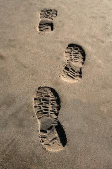 茶色の砂浜のビーチの背景にフットプリントの靴