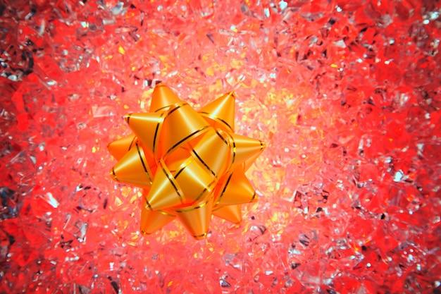 赤い氷の上のクリスマスギフトゴールデンリボン