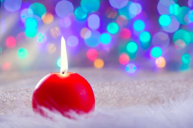 毛皮とカラフルな光の赤いクリスマスキャンドル