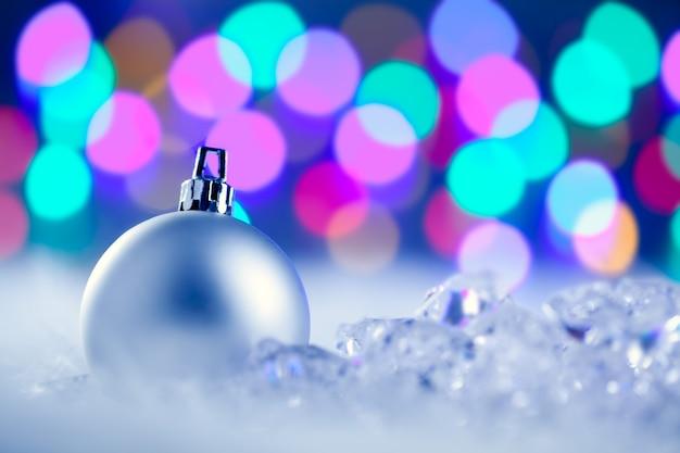 Рождественская серебряная безделушка в размытых огнях