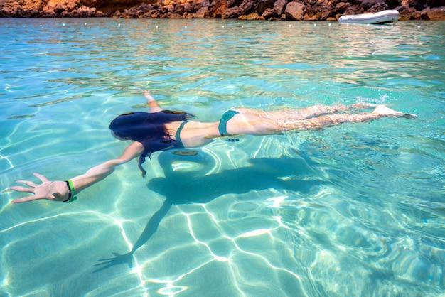 澄んだ水のビーチを泳ぐイビサビキニの女の子