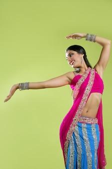 美しいインドの若いブルネットの女性のダンス