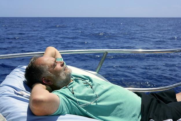 夏のボートで休憩を持つ船員年配の男性