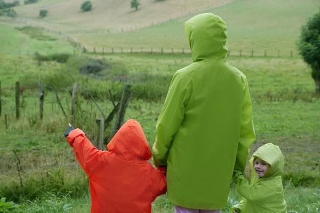 防水カラフルなコートが付いている緑の牧草地