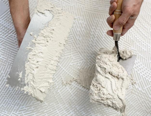 Зубчатый шпатель и рабочие руки на плитке