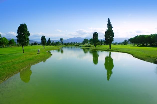 ゴルフ場の緑の芝生フィールド湖の反射