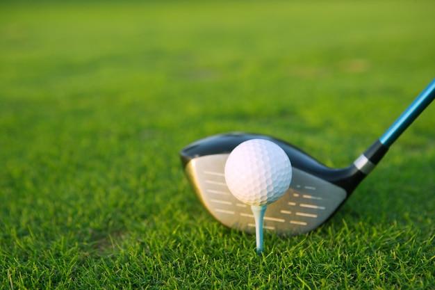 緑の芝生コースのゴルフティーボールクラブドライバー