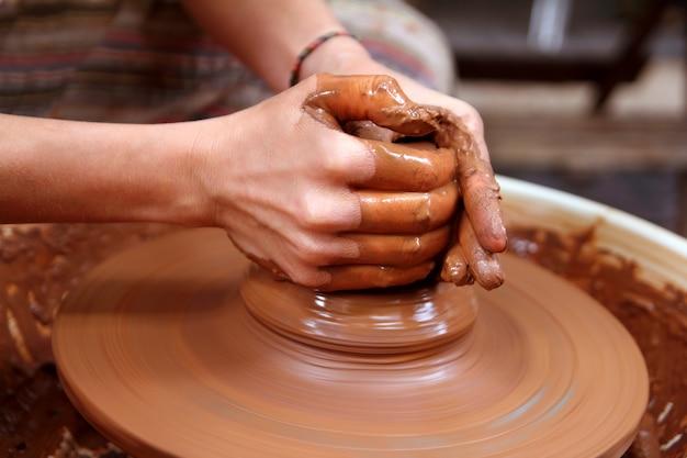 粘土陶芸家の手のクローズアップ、ホイール工芸品に取り組んで