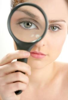 目に拡大鏡のレンズを持つ女性