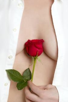 赤いバラを保持している美しい女性の体