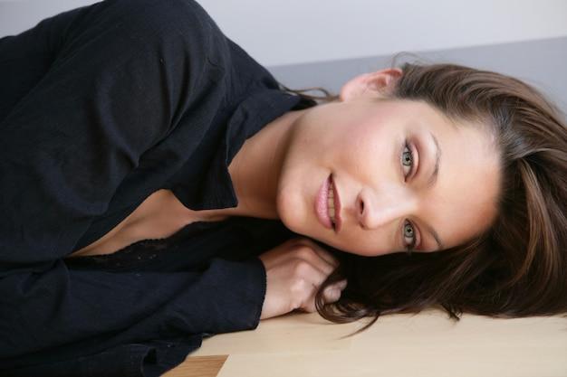Красивые голубые глаза женщины, платье на черном