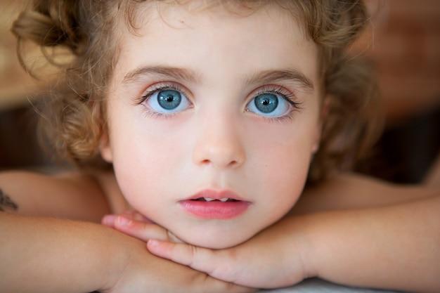 カメラを見て大きな青い目の幼児の女の子