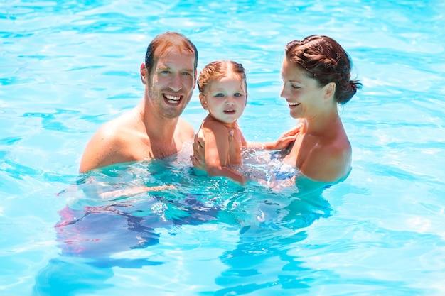 女の赤ちゃんのスイミングプールで幸せな家族