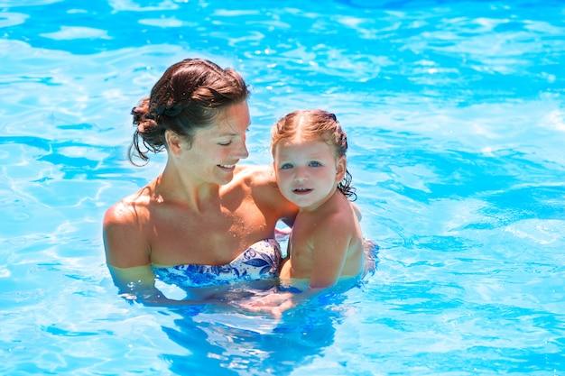 幸せな母親と赤ちゃんの娘のプール