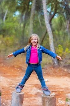 子供の女の子が両手を広げて木の幹を登る