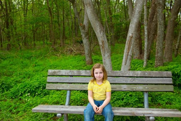 孤独な子供女の子幸せな公園のベンチに座っています。