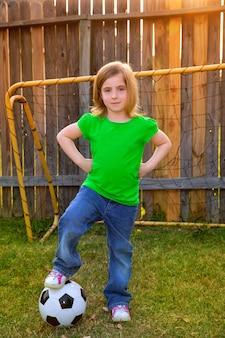 裏庭で幸せな金髪の小さな女の子サッカー選手