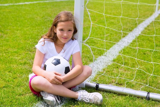 サッカーサッカー子供の女の子がボールを持つ草でリラックス