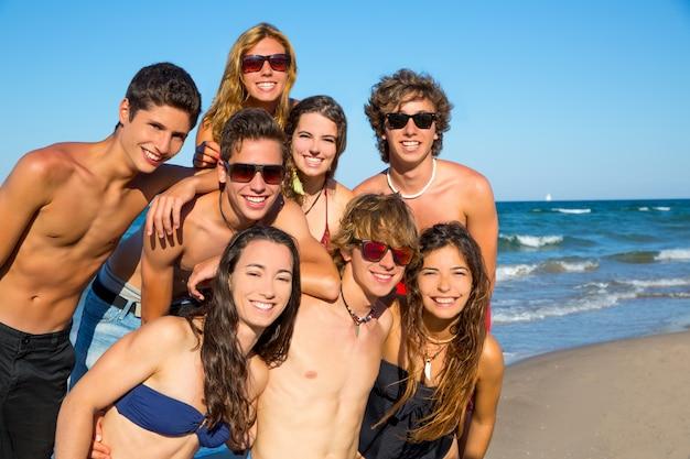 ビーチで一緒に幸せなティーンエイジャーの若いグループ