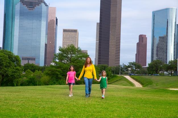 母と娘が街のスカイラインに手をつないで歩く