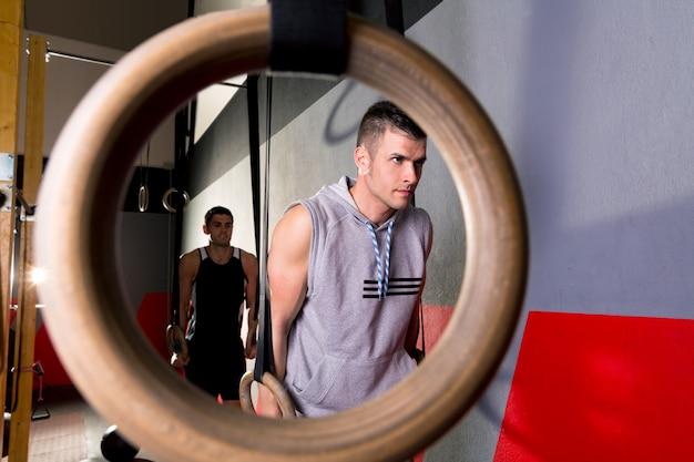 ジムでリングの穴からディップリングトレーニング男