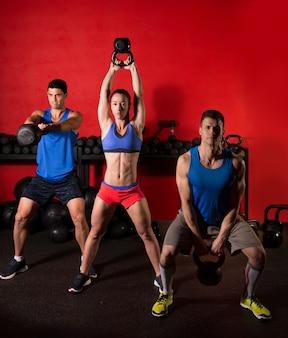 Тренировочная группа по размаху гирей в спортзале