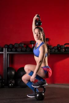 ケトルベルの赤いジムで女性トレーニングを持ち上げる