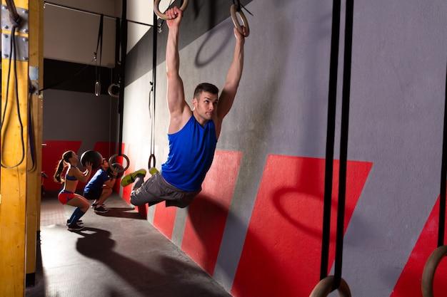 筋肉アップリングの男がジムでエクササイズをスイング
