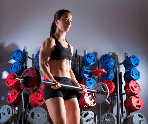 重量挙げのジムでバーベル女性トレーニングフィットネス