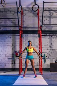 ジムでバーベルの重量挙げの女性重量挙げ