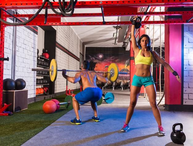 バーベルの重量挙げの男性女性ライジングケトルベル