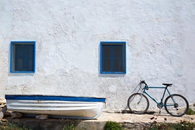 Средиземноморская лодка велосипед и белая стена в белом
