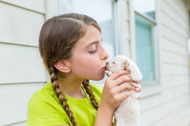 Девочка играет поцелуй щенка чихуахуа любимая собака