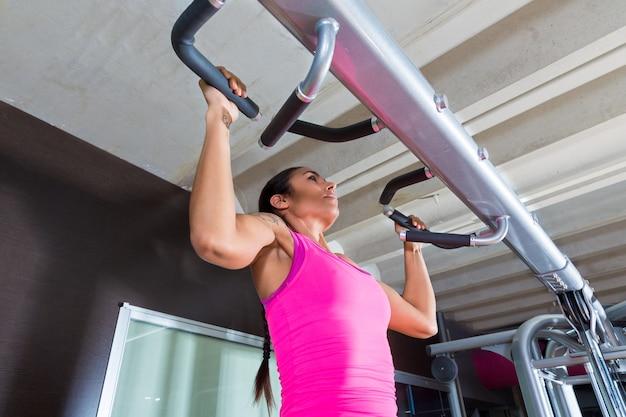 ジムのエクササイズでプルアップ運動トレーニングの女の子