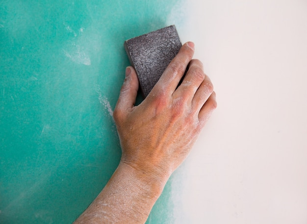乾式壁の継ぎ目にプラスターを研磨男の手を左官工事