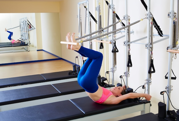 ピラティスリフォーマーの女性の長い背骨運動