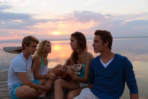 サンセットビーチでギターを楽しんで友達グループ