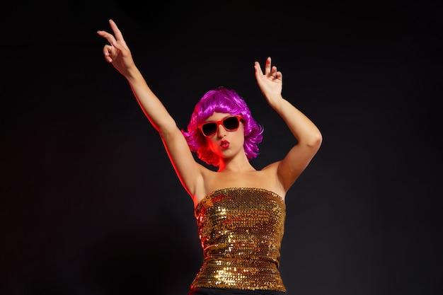 赤いメガネとパーティーを踊る楽しい紫色のかつらの女の子