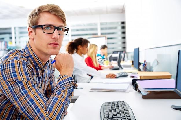 コンピューターのオフィスで若い金髪の実業家