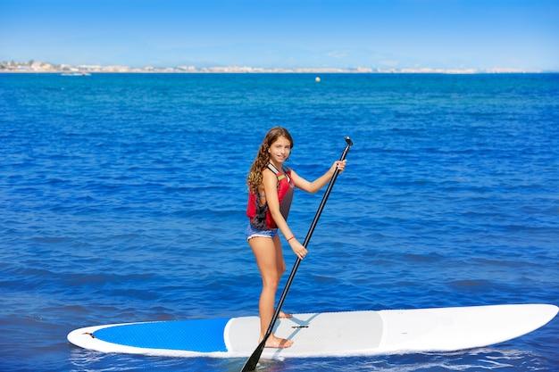 ビーチで行を持つ子供パドルサーフィンサーファーの女の子