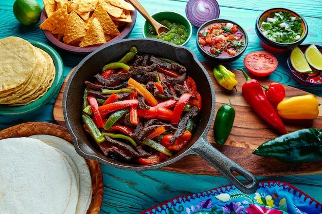 Фахитас из говядины в сковороде соусы чили и гарнир мексиканский