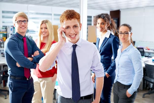 Молодой исполнительный разговаривает по телефону в многонациональной команде