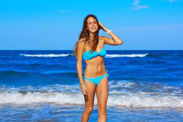 ビーチの海岸を歩いてブルネットの幸せな女の子