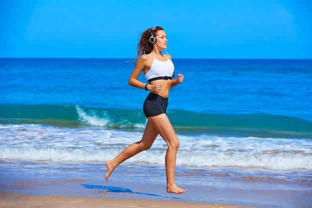 夏のビーチを走る美しいブルネットの少女