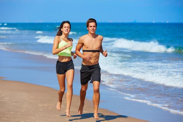 夏のビーチを走るカップル若い